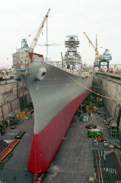 A port bow view of the battleship USS NEW JERSEY (BB-62) in dry dock undergoing refitting and reactivation