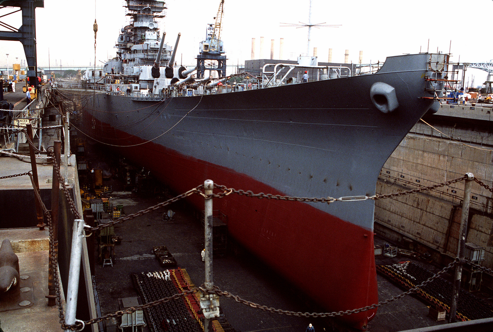 A starboard bow view of the battleship USS NEW JERSEY (BB-62) in drydock. The ship is undergoing refitting and reactivation