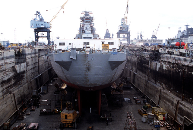A stern view of the battleship USS NEW JERSEY (BB-62) in drydock. The ship is undergoing refitting and reactivation