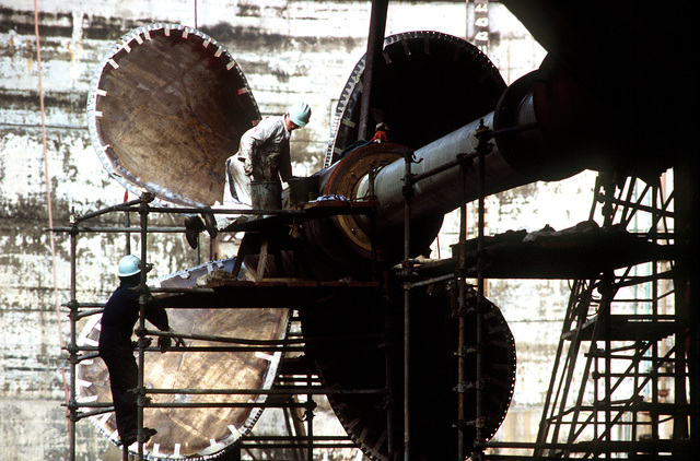 Shipyard personnel lubricate the strut bearings of the starboard screw assembly of the battleship USS NEW JERSEY (BB-62) in drydock. The ship is undergoing refitting and reactivation