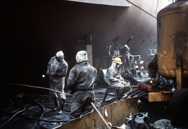 Shipyard personnel wear protective gear as they work on the hull of the battleship USS NEW JERSEY (BB-62), in dry dock being overhauled and refitted for reactivation