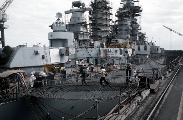 Shipyard workers board the battleship USS NEW JERSEY (BB-62) by way of the starboard gang plank. The NEW JERSEY is in dry dock for overhauling, refitting and reactivation