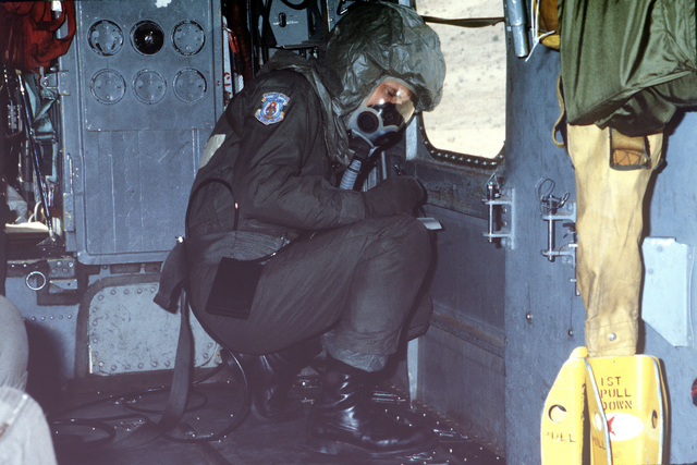 A crew member of a CH-3 helicopter scans his checklist while wearing Chemical Warfare Defense Equipment (CWDE) during a new generation equipment test