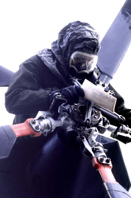 A crew member wearing Chemical Warfare Defense Equipment (CWDE) conducts preflight procedures on a CH-3 helicopter during a new generation equipment test