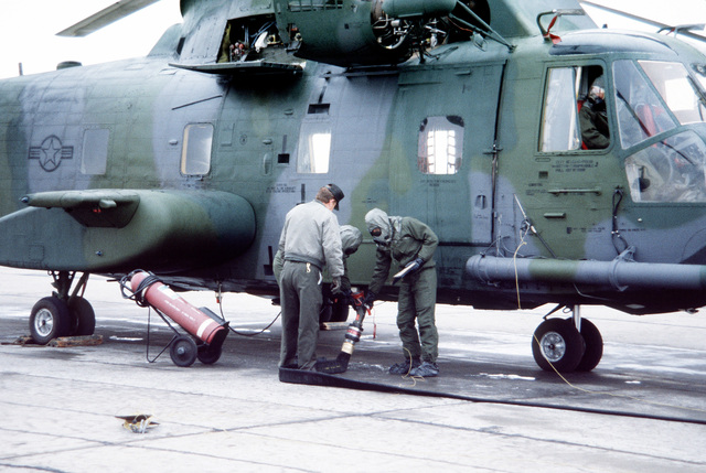 Crew members wearing Chemical Warfare Defense Equipment (CWDE) conduct preflight procedures on a CH-3 helicopter during a new generation equipment test