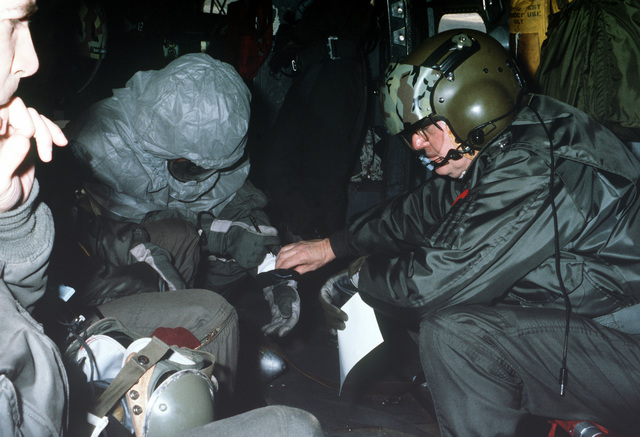 LTC Larkin, flight surgeon, checks crew members wearing Chemical Warfare Defense Equipment (CWDE) as they fly in a CH-3 helicopter, during a new generation equipment test