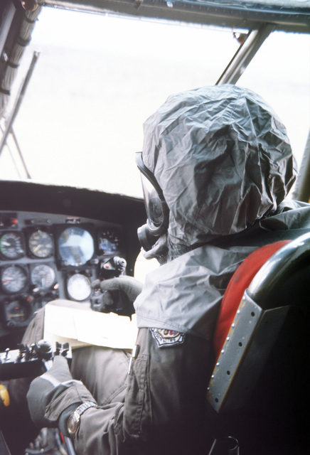 The pilot in the cockpit of a CH-3 helicopter wears Chemical Warfare Defense Equipment (CWDE) during a new generation equipment test