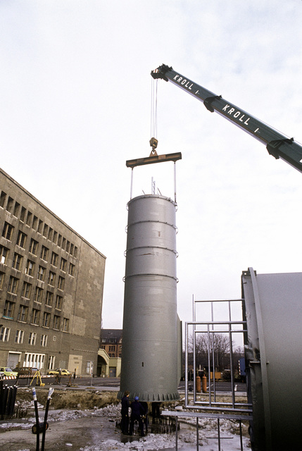 A construction crew installs one of the supporting legs for the new radar system