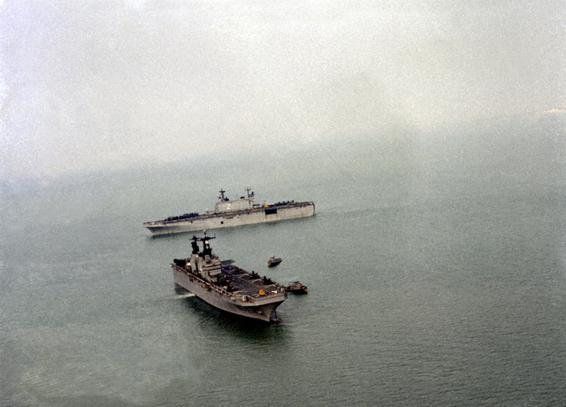 The passing of the amphibious assault ship USS NASSAU (LHA-4), in the foreground, and the amphibious assault ship USS SAIPAN (LHA-2) takes place during the turnover of Task Force 61 duties. NASSAU, the flagship for Marine Amphibious Ready Group (MARG) 1-82 relieves the SAIPAN, the flagship for MARG 3-81