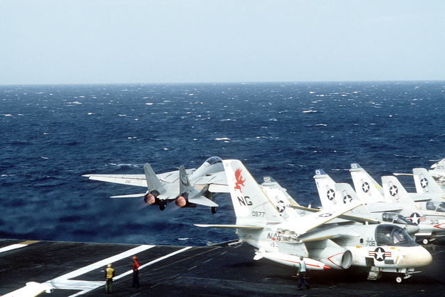 A rear view of an F-14 Tomcat fighter aircraft taking off from the aircraft carrier USS CONSTELLATION (CV-64). In the right foreground is a parked S-3 Viking anti-submarine aircraft from Carrier Air Wing 9 (CVW-9)