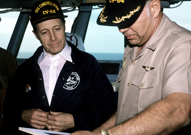 CAPT D.M. Brooks, commanding officer, briefs Secretary of Defense Caspar Weinberger, left, during his visit aboard the aircraft carrier USS CONSTELLATION (CV-64)