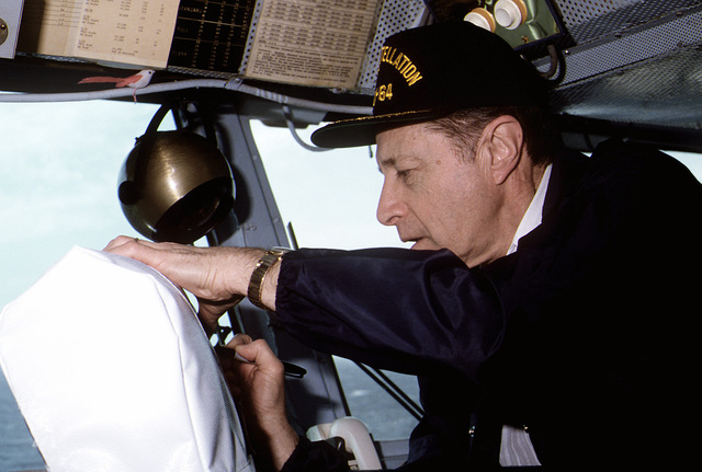 Secretary of Defense Caspar Weinberger autographs the back of a chair on the bridge during a visit to the aircraft carrier USS CONSTELLATION (CV-64)