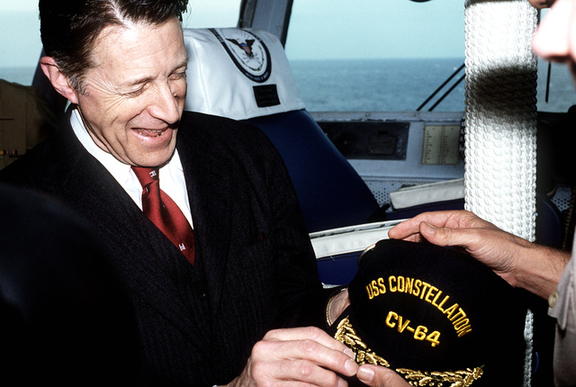 Secretary of Defense Caspar Weinberger is presented with a ship's cap upon his arrival aboard the aircraft carrier USS CONSTELLATION (CV-64) for a visit