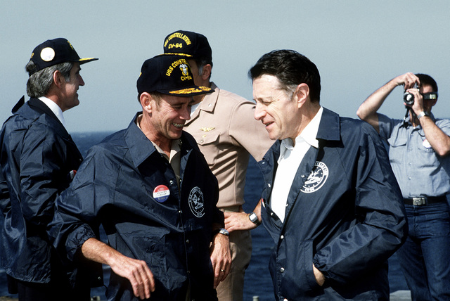 Secretary of Defense Caspar Weinberger, right, talks to RADM George Aircheson Jr., commander of Carrier Group 7, during a visit aboard the aircraft carrier USS CONSTELLATION (CV-64)