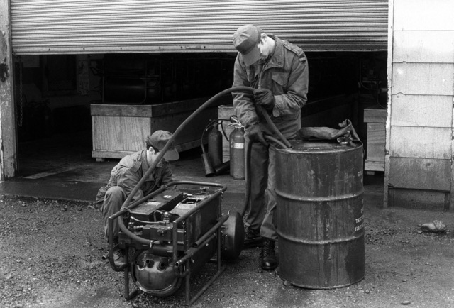 SSGT Clifford Hoffman, 164th Smoke Generator Detachment, adjusts an M-3A3 smoke generator valve while PFC Frank Robbins leads hoses into a 4-gallon barrel of fog oil in preparation for starting the M-3A3 for a demonstration