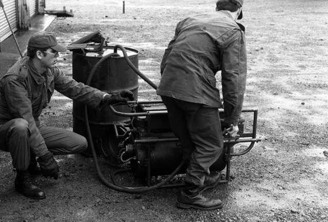 SSGT Clifford Hoffman, 164th Smoke Generator Squadron, adjusts the M-3A3 smoke generator valve with a wrench while PFC Frank Robbins reaches for the gas flow valve in preparation for starting the M-3A3 for a demonstration