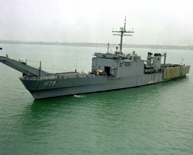 A port bow view of the tank landing ship USS NEWPORT (LST-1179) leaving port after a visit
