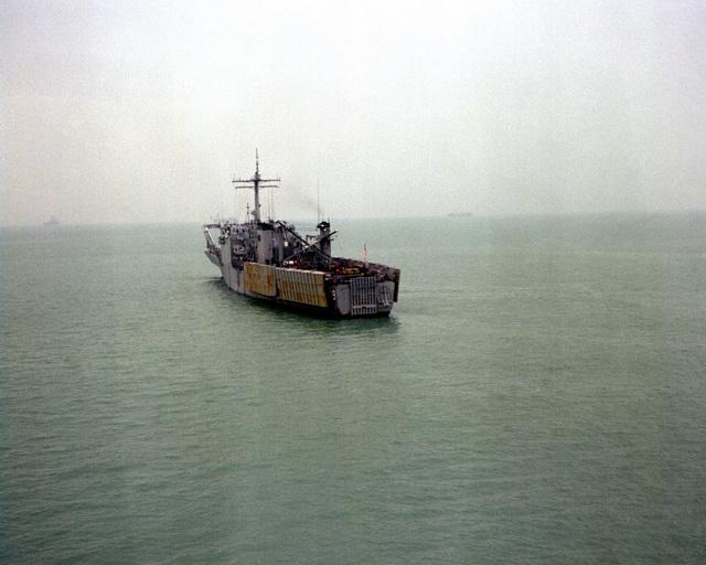 A port quarter view of the tank landing ship USS NEWPORT (LST-1179) leaving after a port visit