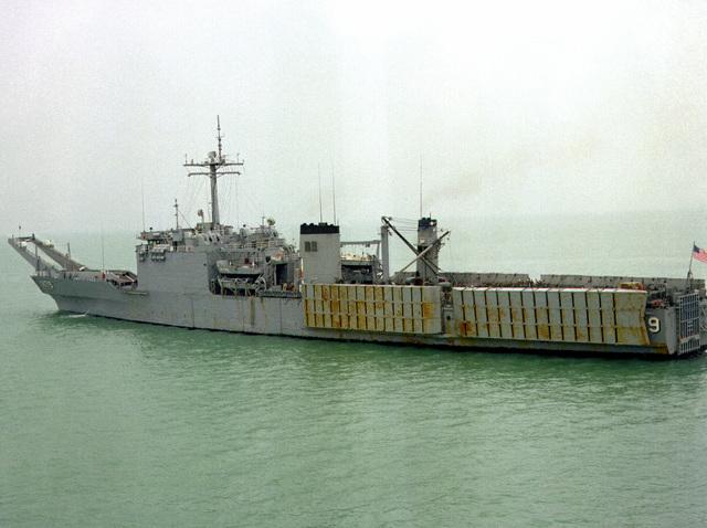 A port quarter view of the tank landing ship USS NEWPORT (LST-1179) leaving port after a visit