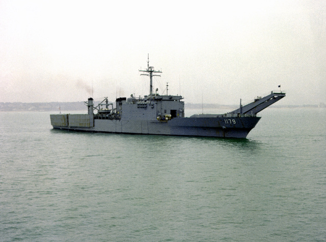 A starboard view of the tank landing ship USS NEWPORT (LST-1179) leaving after a port visit