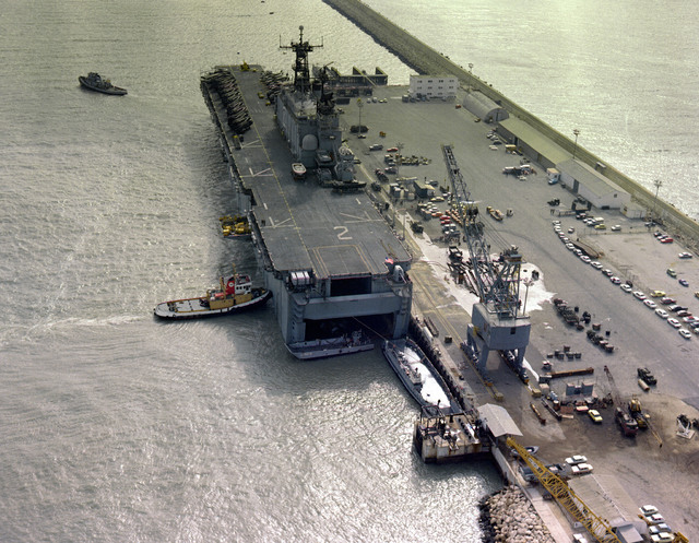 A stern view of the amphibious assault USS SAIPAN (LHA-2) being maneuvered into docking position by tugs