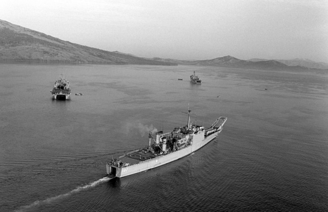 An aerial starboard quarter view of the Newport-class tank landing ship USS FRESNO (LST 1182) underway while supporting a Marine Corps amphibious beach assault exercise