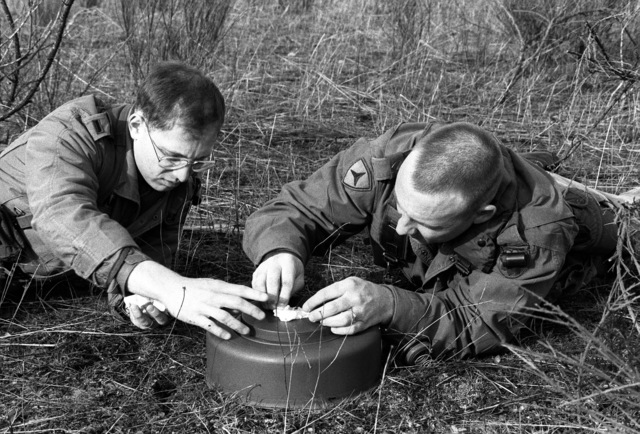 1LT Marc Hildenbrand and SSGT Larry Kemp of Company A, 15th Engineering Battalion, pack C4 into the well of an M-15 anti-tank mine around a detonation cap during an exercise at Range 60