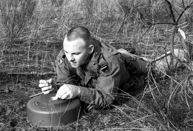 SSGT Larry Kemp of Co. A, 15th Eng. Bn., packs C4 into the well of an M-15 anti-tank mine prior to inserting a detonation cap during an exercise at Range 60