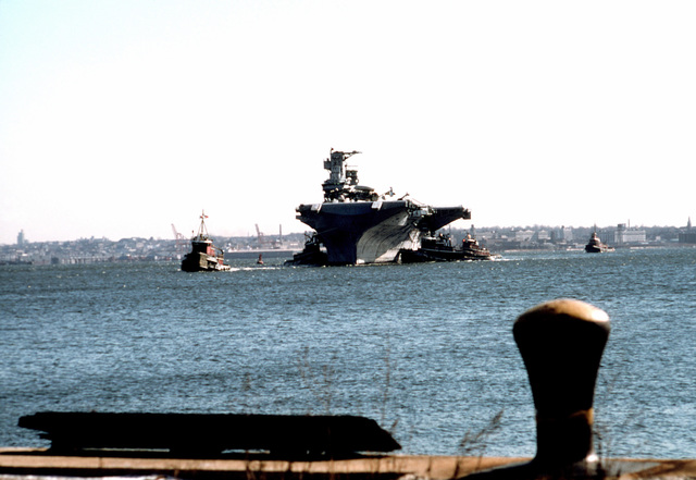 A bow view of the anti-submarine warfare support aircraft carrier ex-USS INTREPID (CVS-11) being maneuvered into docking position by tug boats. The INTREPID is being towed to Bayonne, N.J., to be refitted and opened to the public as a museum in New York