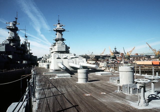A view from forward looking aft at No.s 1 and 2 16-inch/50-caliber gun turrets and the bridge of the battleship IOWA (BB-61). The ship is in mothball storage here