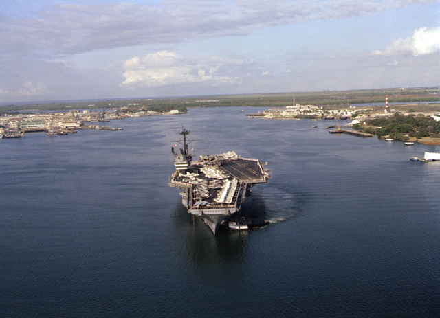 A bow view of the aircraft carrier USS RANGER (CV-61) being maneuvered into docking position by a tug at the port bow
