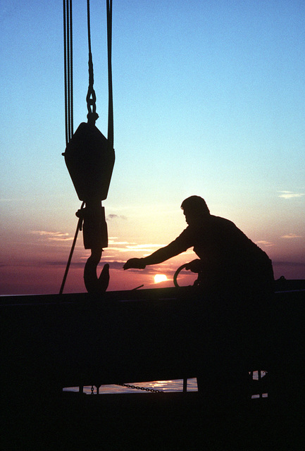 A crewman lowers a hook to load supplies aboard the surveying ship USNS CHAUVENET (T-AGS-29) during an expedition to update present navigation charts of the strait