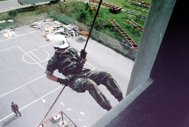 A member of the Security Police Emergency Services Team (EST) rappels down a five story training tower during training exercises