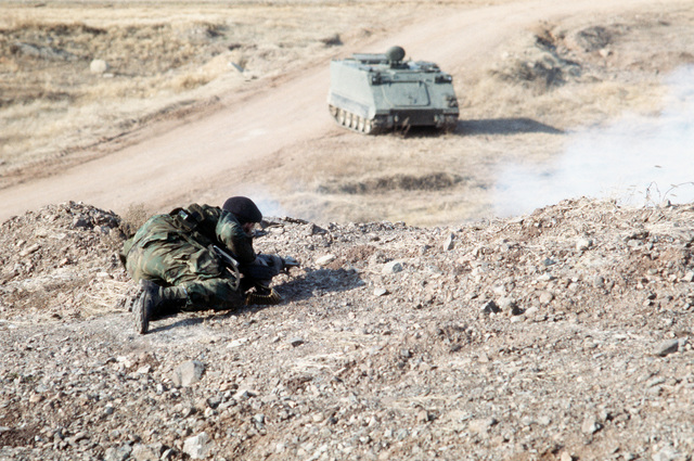 A soldier, armed with an M-60 machine gun, helps defend the boundaries of the air field from aggressor forces during exercise Team Spirit '82. Below him an armored personnel carrier moves across the terrain