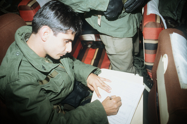A soldier from the 25th Infantry Division, a participant in Exercise Team Spirit '82, fills out a customs form prior to debarking the B-747 aircraft
