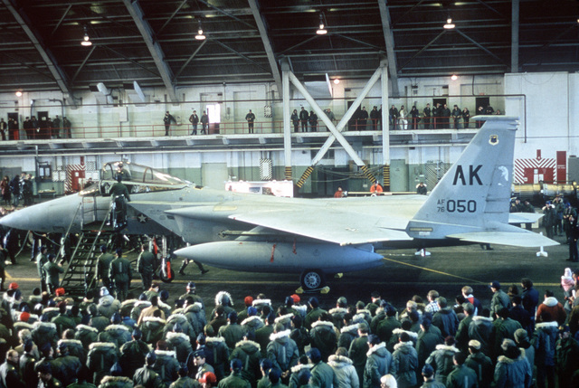 A view of an F-15 Eagle aircraft in a hangar, as Air Force members look on