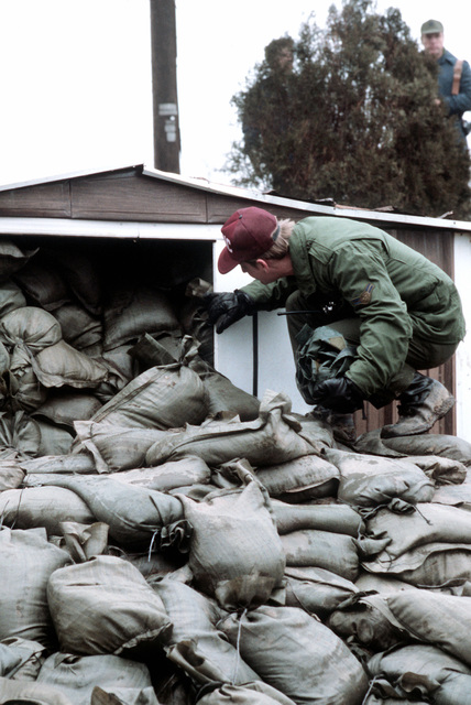 A1C Robert Spence, from the Clinical Material Section at Grissom Air Force Base, checks one of the buildings at the Pemberton dike, which was reinforced with sandbags after a recent flood