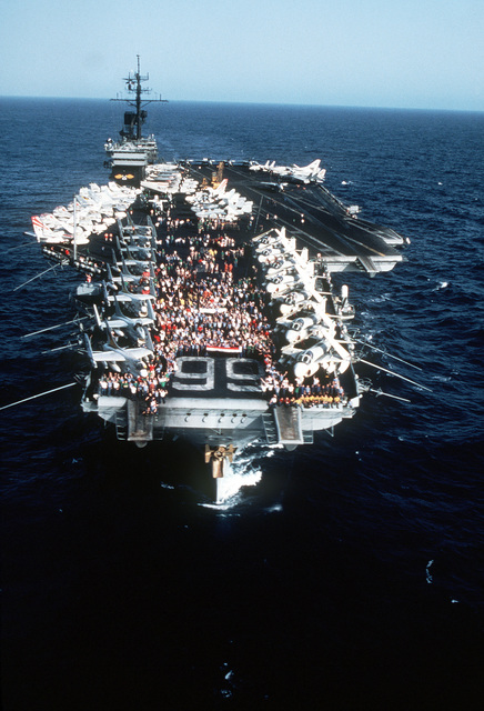 An aerial bow view of the aircraft carrier USS AMERICA (CV-66) with its crewmen gathered on the flight deck