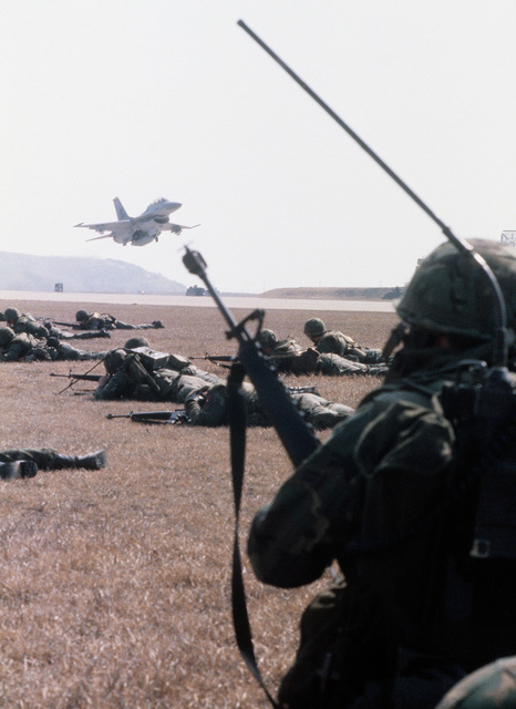 An F-16 Fighting Falcon aircraft takes off as members of the 3380th Security Police Squadron, foreground, defend the air field from aggressor forces during exercise Team Spirit '82