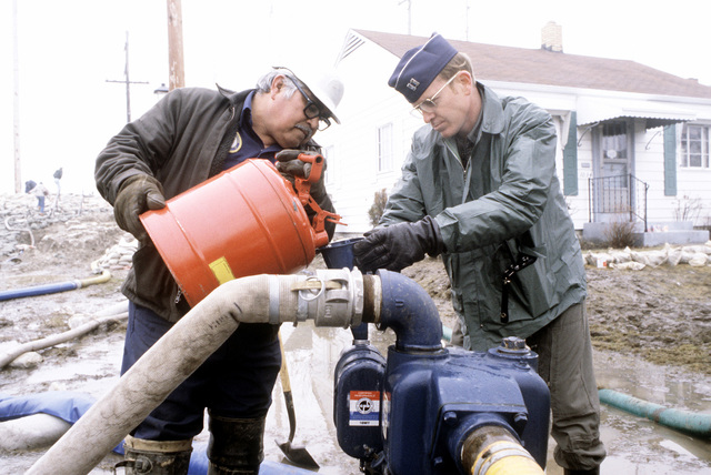 Raymond Rodrigez, a city worker, and CPT Stan Norris of the 70th Aerial Refueling Squadron (70th ARS) Grissom Air Force Base, refuel one of the many water pumps used to pump water from area streets and homes after a recent flood