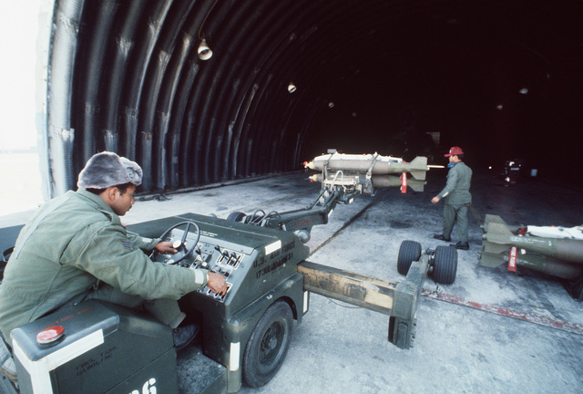 SGT Donnie McGabe operates a bomb loader, as A1C Daniel Franquez gives directions. The bomb loader is being used to move Mark 82 bombs into position to be loaded aboard an F-4G Advanced Wild Weasel aircraft. The men are participating in Exercise Team Spirit '82
