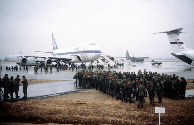 Soldiers from the 25th Infantry Division prepare to board the buses (not visible) that will transport them to their operating locations for Exercise Team Spirit '82