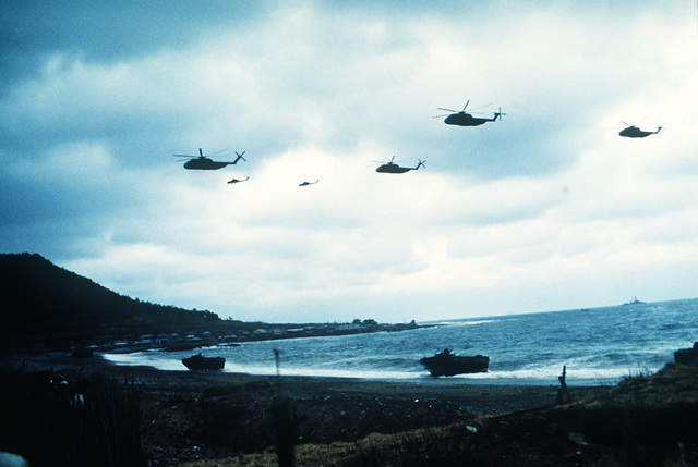 Two AH-1 Sea Cobras (background) and four H-53 Sea Stallion helicopters from the amphibious assault ship fly troops inland during Exercise Team Spirit '82