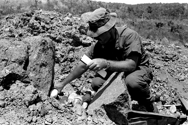 A member of a US Navy Explosive Ordnance Disposal unit places mortar rounds between two large rocks prior to detonating them during an ordnance disposal exercise