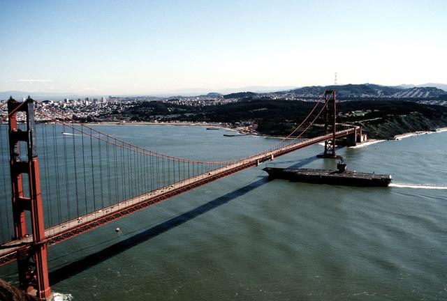 A port beam view of the nuclear-powered aircraft carrier USS ENTERPRISE (CVN-65) steaming under the Golden Gate Bridge