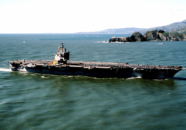 A starboard beam view of the nuclear-powered aircraft carrier USS ENTERPRISE (CVN-65) approaching the entrance to the San Francisco Bay