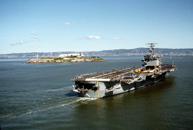 A starboard quarter view of the nuclear-powered aircraft carrier USS ENTERPRISE (CVN-65) underway with Alcatraz off the port side