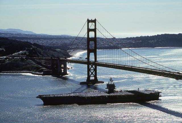 An aerial port beam view of the nuclear-powered aircraft carrier USS ENTERPRISE (CVN-65) just after steaming beneath the Golden Gate Bridge
