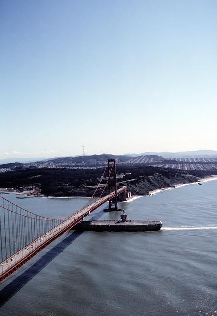 An aerial port beam view of the nuclear-powered aircraft carrier USS ENTERPRISE (CVN-65) steaming beneath the Golden Gate Bridge