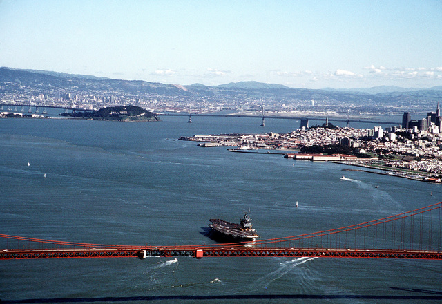 An aerial port quarter view of the nuclear-powered aircraft carrier USS ENTERPRISE (CVN-65) underway. The Golden Gate bridge is in the foreground